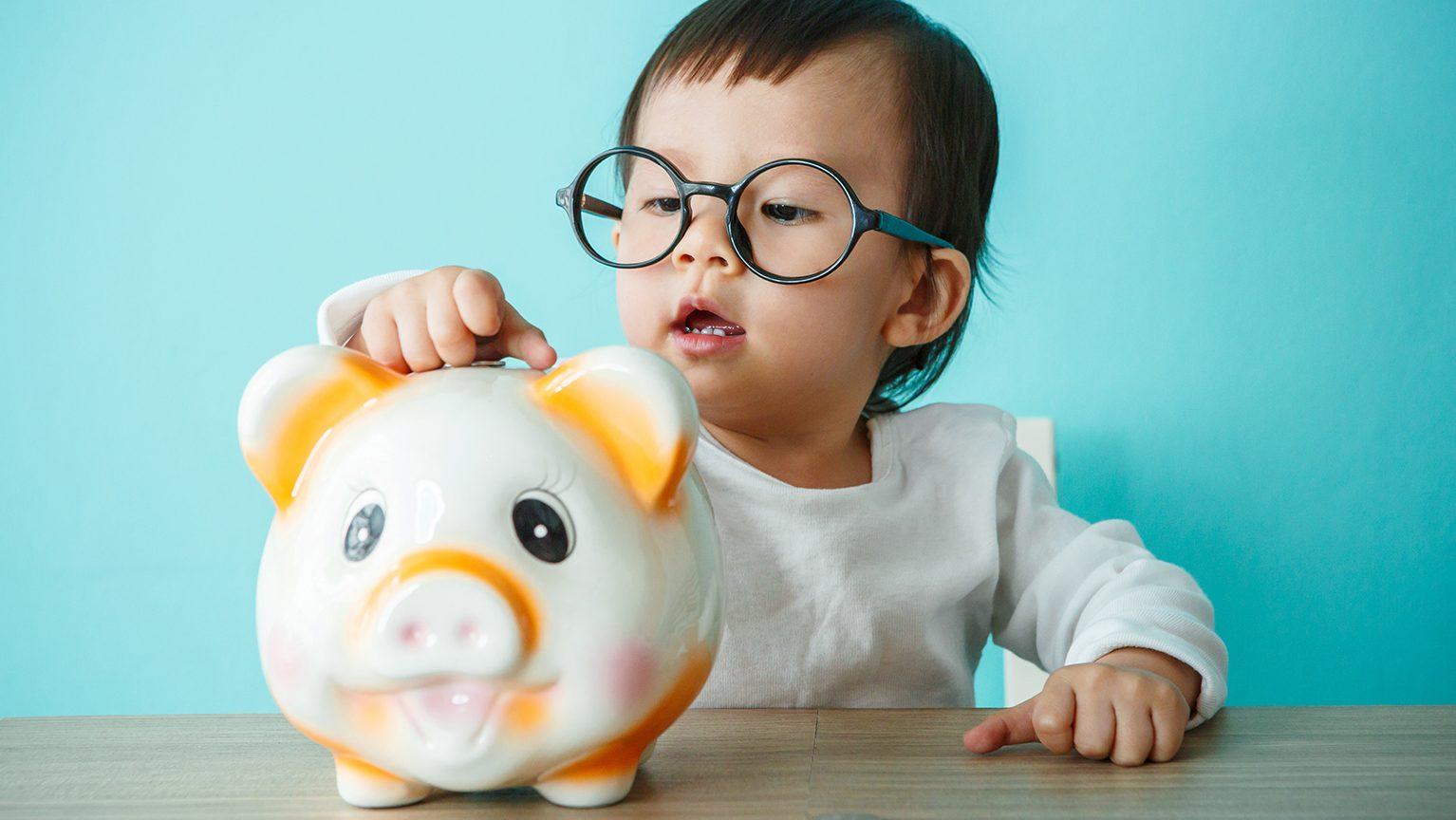 豚の貯金箱に貯金する赤ちゃん
