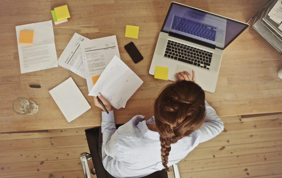 デスクにPCと書類を広げて仕事をする女性