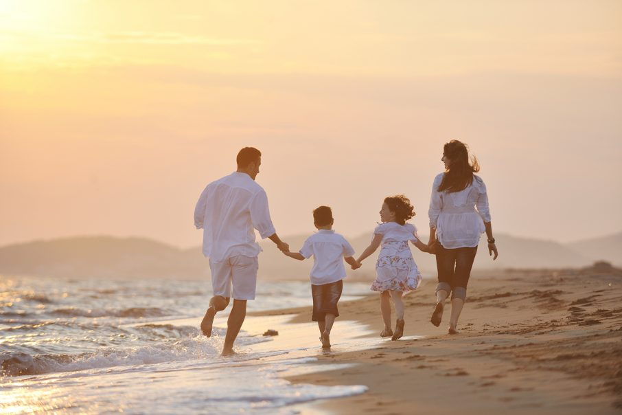 海辺を歩く家族