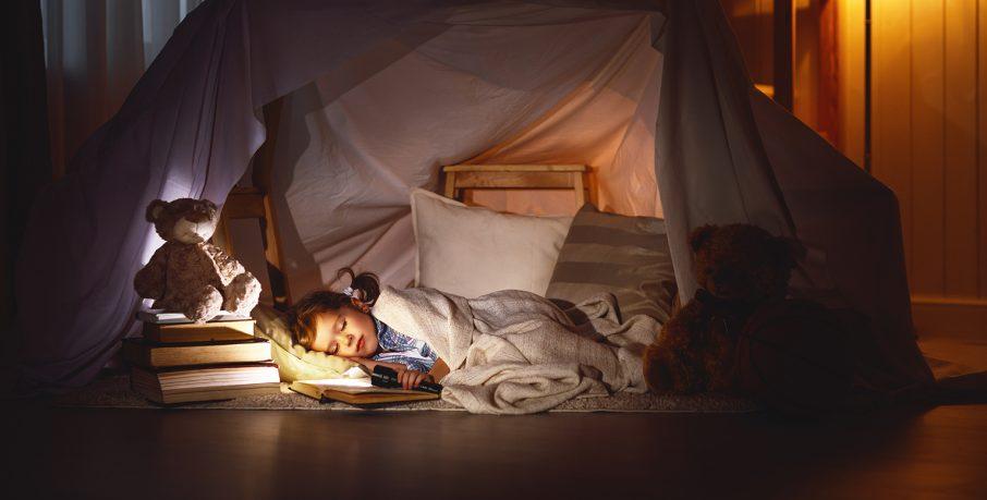 本を読みながら眠る子
